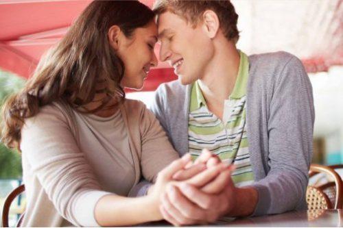 Verliebtes Paar händchenhaltend im Cafe